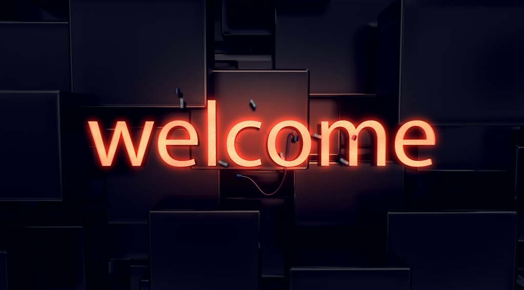 "dark background with the word ""welcome"" written in all lower case neon orange letters"